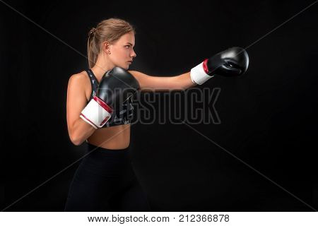 Beautiful female athlete in boxing gloves, in the studio on a black background. The boxer fulfills the blow