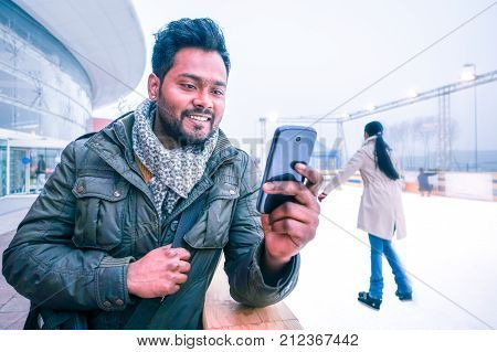 Happy indian man looking mobile phone outdoors at winter with ice skating scene background - Cheerful bangladeshi young guy using cellphone smiling looking telephone screen outside on grey light day