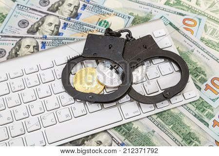 Moscow Russia - November 5 2017: Steel handcuffs and coins of cryptocurrency lying over computer keyboard