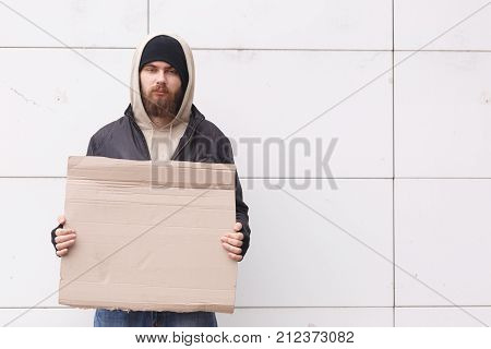 A homeless man stands near a white wall in the street in cold weather with a cortical tablet. Outdoor.