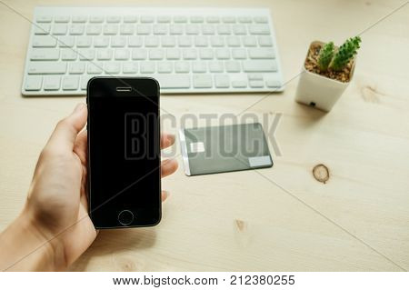 Hand Of Business Woman Hold Smart Phone Has Credit Card, Keyboard And Cactus Placed On Wood Table Ar