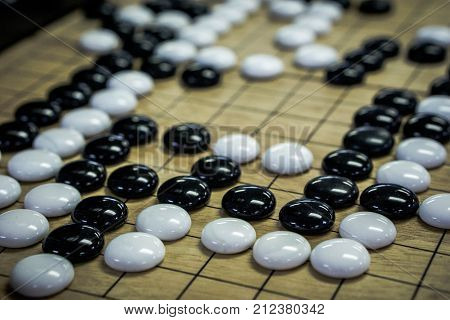 Go. Traditional asian strategy board game.  black and white stone of Chinese go game board.