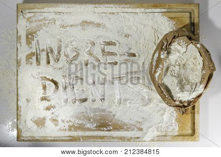 Rough wooden rectangular used cutting board background with paper sack of flour and ingredients word inscribed with finger directly from above on white background