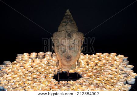 Zen buddhism. Soft serene image of a traditional buddha head statue illuminated by candles. Enlightenment and spirituality.