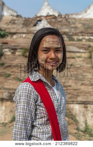 MANDALAY MYANMAR - MARCH 12 : Unidentified Burmese girl with traditional thanaka on her face on March 12 2016 in Mandalay Myanmar.