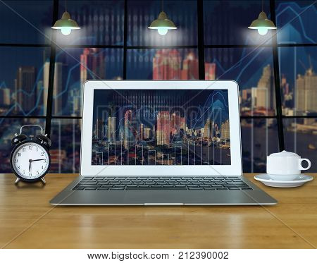 Workspace with computer laptop on the wood table which shown trading graph on the blurred photo of cityscape building background over the screen trading technology concept