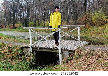 A woman in a yellow coat is standing on a birch bridge in the estate of Count Leo Tolstoy in Yasnaya Polyana.