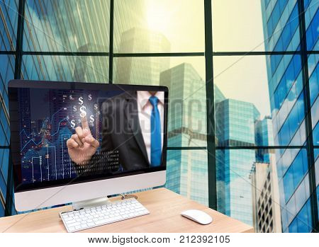 the computer on the wood table with Businessman point sign of money on the trading graph at the screen in front of the glass window over the blurred photo of cityscape background, 3D illustration