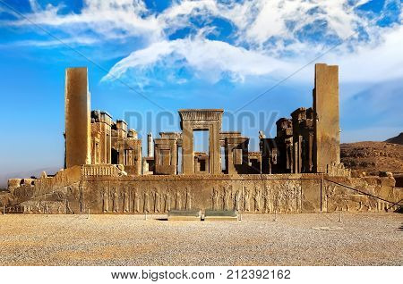 Persepolis is the capital of the ancient Achaemenid kingdom. Sight of Iran. Ancient Persia. Blue sky and clouds background.