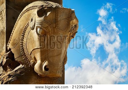 Stone sculpture of a horse in Persepolis against a blue sky with clouds. The Victory symbol of the ancient Achaemenid Kingdom. Iran. Persia. Shiraz.