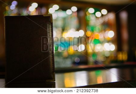 Mock up Menu frame on the blurred background of the bar. Closed Menu book in leather cover with metal corners on the bar table of the restaurant closeup