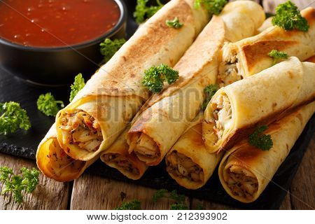 Mexican Taquitos With Chicken And Chili Sauce Close-up. Horizontal