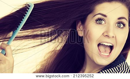 Woman combing her healthy hair using comb. Young latin female with beautiful natural brown straight long hairs toned image