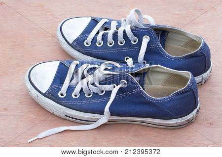 pars of canvas blue shoes on the wood background dirty blue shoes