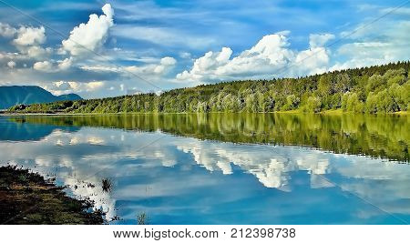 Beautiful bay to the Liptovska Mara dam with the mirroring of the trees on the water surface. Trees mirroring on the water level. Summer scenery in Slovakia.