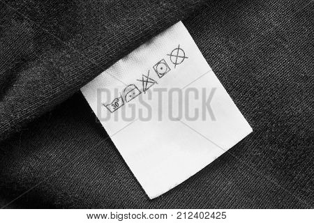 Washing instructions clothes label on black textile background closeup