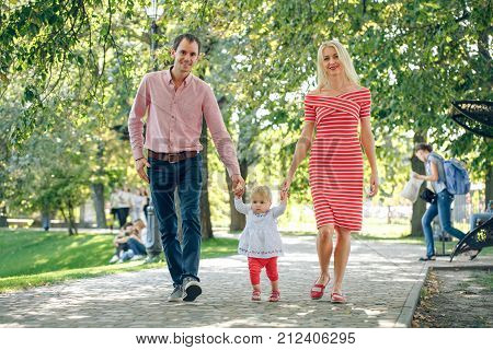 Family walking in the park. mom and daddy going hand in hand with a baby. Parents are taught to walk baby