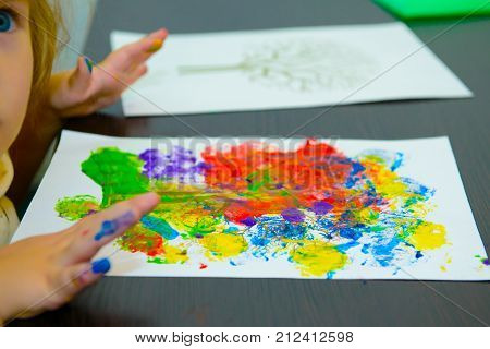 Child draws paints on paper. Children's art drawing. The development of young children and their talents.