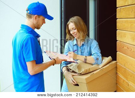 Smiling delivery man in blue uniform delivering parcel box to recipient - courier service concept. Smiling delivery man in blue uniform poster