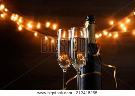 Festive photo of two wine glasses with wine, bottles, cork, burning garland