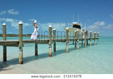 Girl on the wooden jetty looking to the ocean, Bahamas