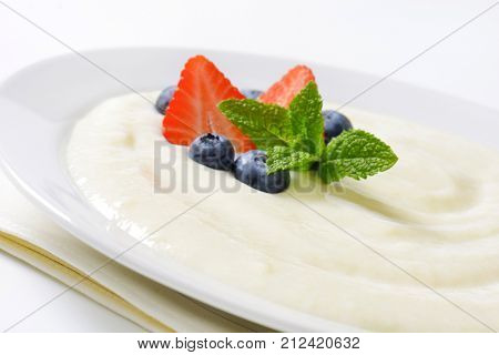 plate of semolina pudding with fresh fruit - close up