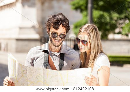 Happy tourists couple holding a city map