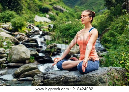 Woman meditate in Hatha yoga asana Padmasana outdoors at tropical waterfall