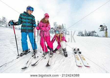 Mom with children on ski terrain preparing daughters ski shoes for skiing