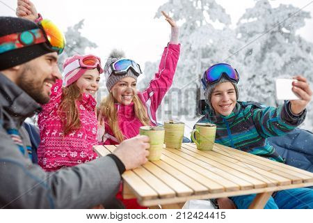 Happy skiing family in cafe drinking tea and making photo while resting