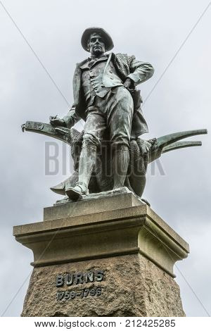 Sydney Australia - March 23 2017: Closeup of figure on top of pedestal an all bronze statue of Robert Burns on side of Vernon building of Art Gallery of NSW. Against silver sky.