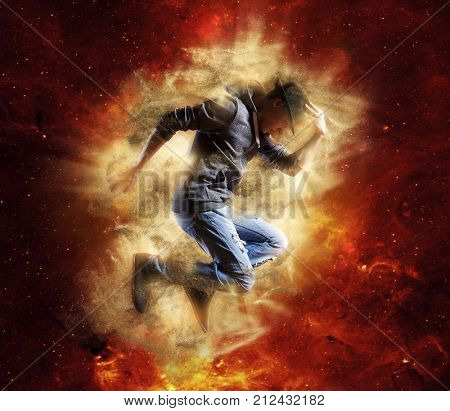 Young man break dancing on gold background