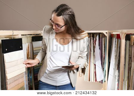 Young woman with fabric samples for curtains in drapery shop