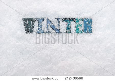 The word WINTER made from wooded letterpress letters on a snow background