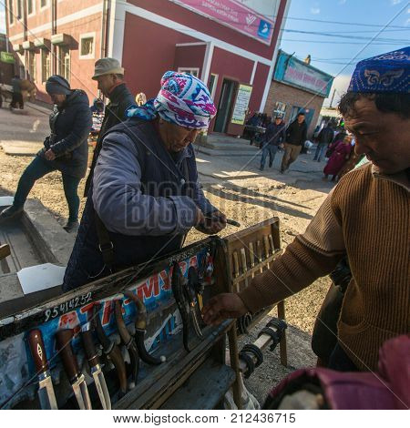 OLGIY, BAYAN-OLGIY, MONGOLIA - SEP 29, 2017: Unknown woman in the city market sells daggers. In Bayan-Olgiy province is populated to 88,7% by Kazakhs.