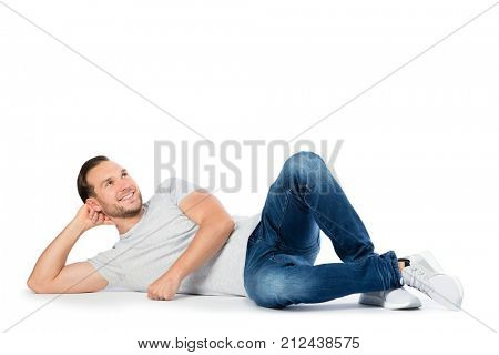 Cheerful man supporting his head on the hand, laying on the floor and looking up. Wandering happy thoughts. Isolated on white background.