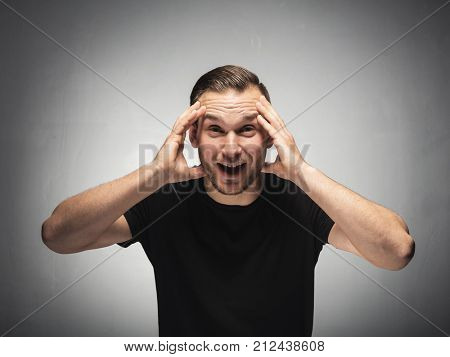 Surprised and astonished man grabbing his head in a shocked gesture. Studio shot.