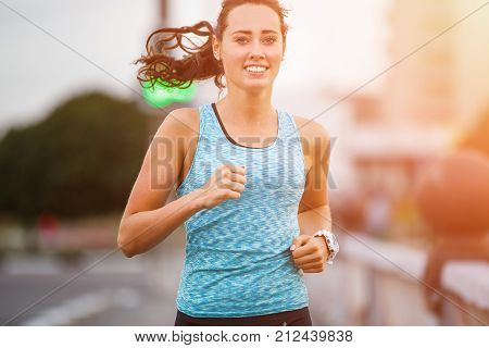 Young smiling woman running on bridge in early morning. Caucasian girl with long hair jogging in a city