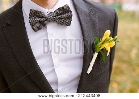 freesia pinned to the lapel of the groom
