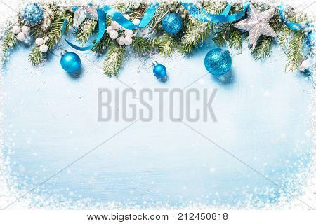 Christmas background. Blue and silver decorations on blue wooden background. Top view copy space. Snow frame.