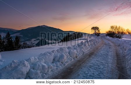 countryside road uphill in snow at sunset. beautiful winter scenery in mountainous area