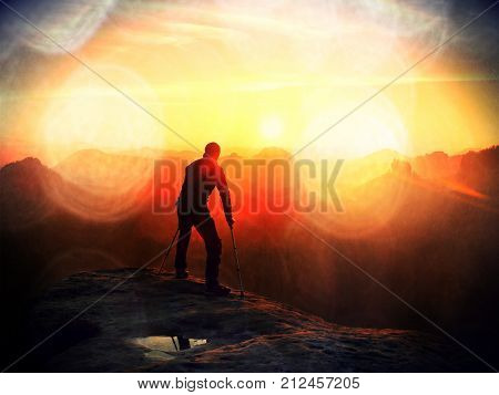 Bended Man With Broken Leg And Medicine Crutch.  Hiker With Leg In Immobilizer Achieve Peak Of Mount