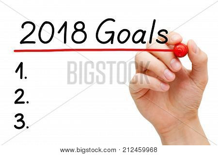 Blank goals list for year 2018 isolated on white. Hand underlining 2018 Goals with red marker on transparent wipe board.