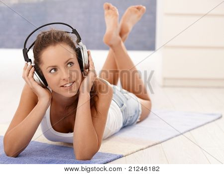 Pretty girl listening to music, using headphones, laying on floor at home, smiling.?