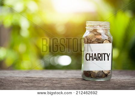 Charity word with coin in glass jar Business Concept.