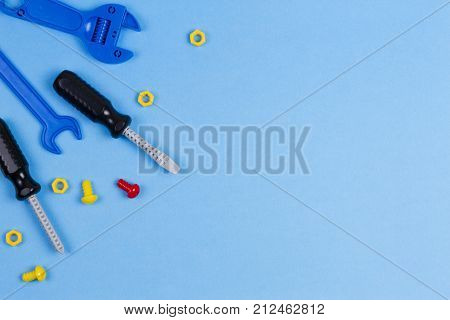 Toys background. Kids toys top view. Toy tools on blue background