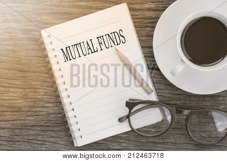 Concept MUTUAL FUNDS message on notebook with glasses pencil and coffee cup on wooden table.