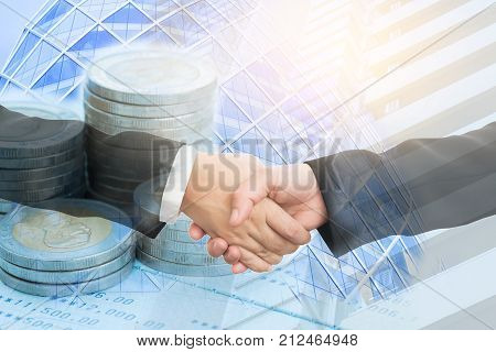 Double exposure of two businesswoman handshake and coins on bank statement with modern city background Finance and banking concept.