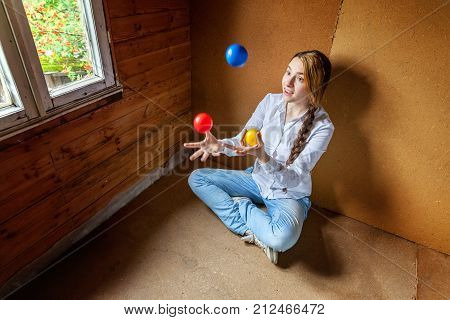 beautiful young smiling woman sitting and juggling poster