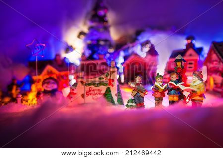 kid gospel choir singing next to Seasons greeting sign with  snowman and christmas village in the background. Fairytale miniature scenery